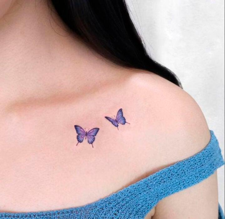 Tatuaje pequeño sobre la clavícula, de dos mariposas color morado