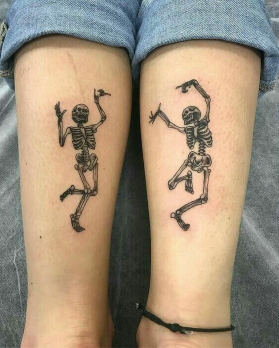 Complementary tattoo of dancing skeletons on the forearm area