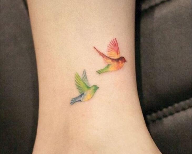 Tatuaje pequeño sobre el tobillo de dos golondrinas