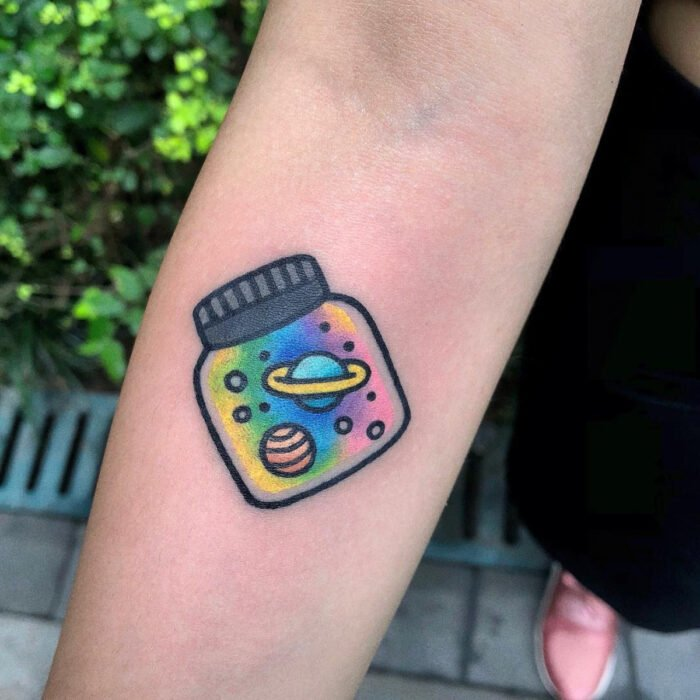Pretty glass jar tattoo designs with rainbows and planets on the arm
