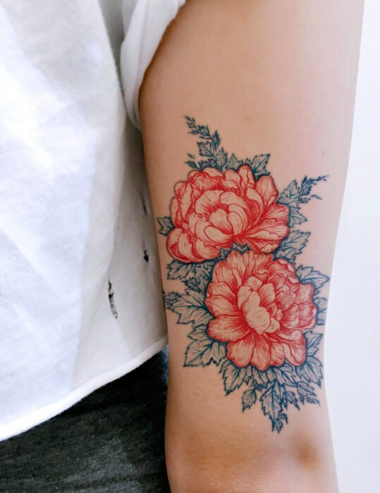 Diseños de tatuajes originales; flores peonias rojas con hojas azules, tatuaje floral en el brazo