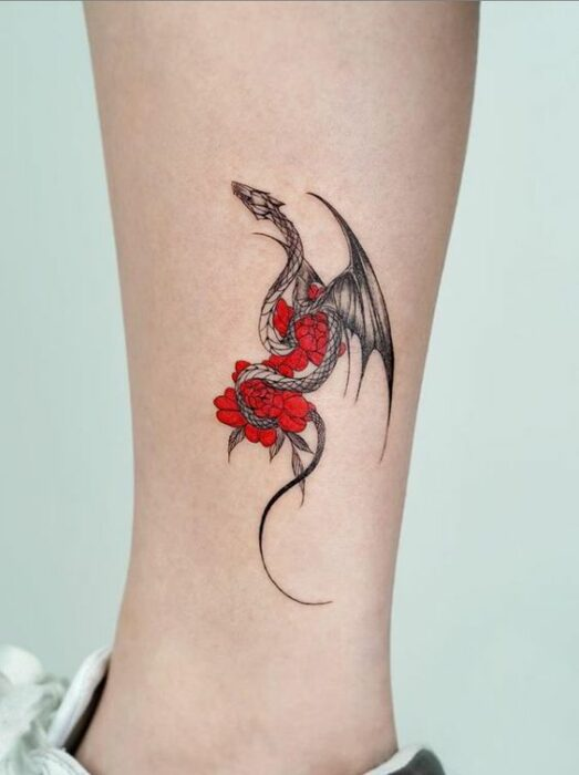 Girl with tattoo of a dragon holding red flowers