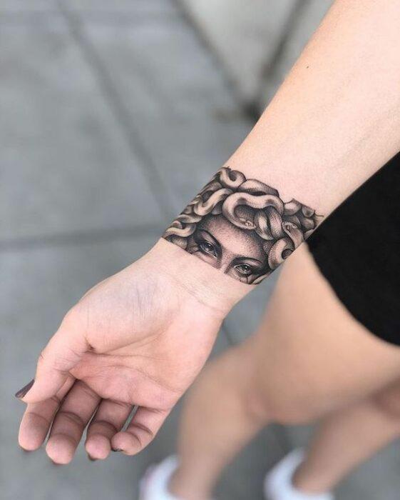 Chica con tatuaje de Medusa en forma de brazalete