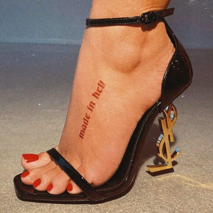 Chica con tatuaje en inglés en el tobillo