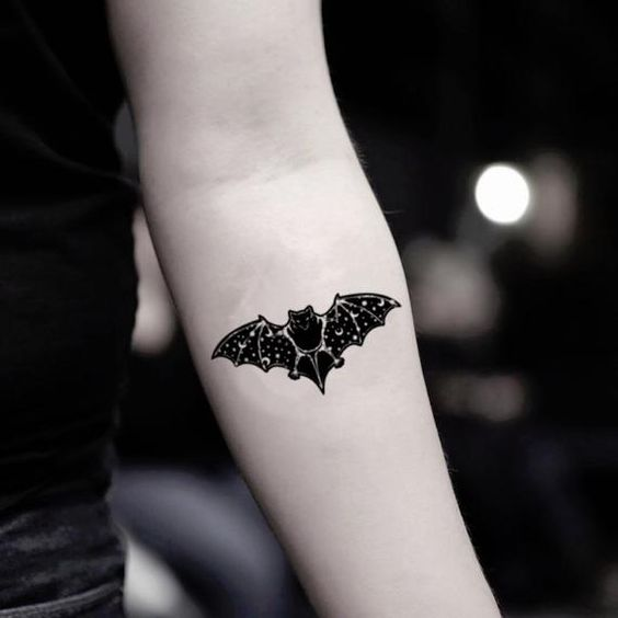 Girl with bat-shaped forearm tattoo
