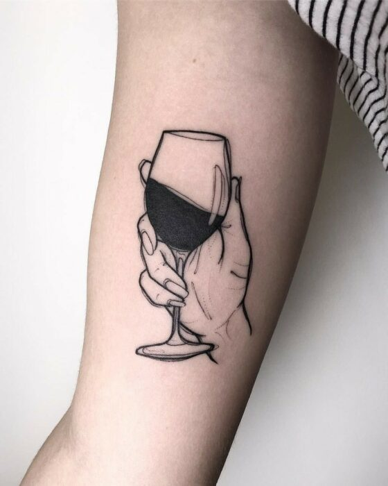 Girl with tattoo of a hand holding a glass of wine on her elbow