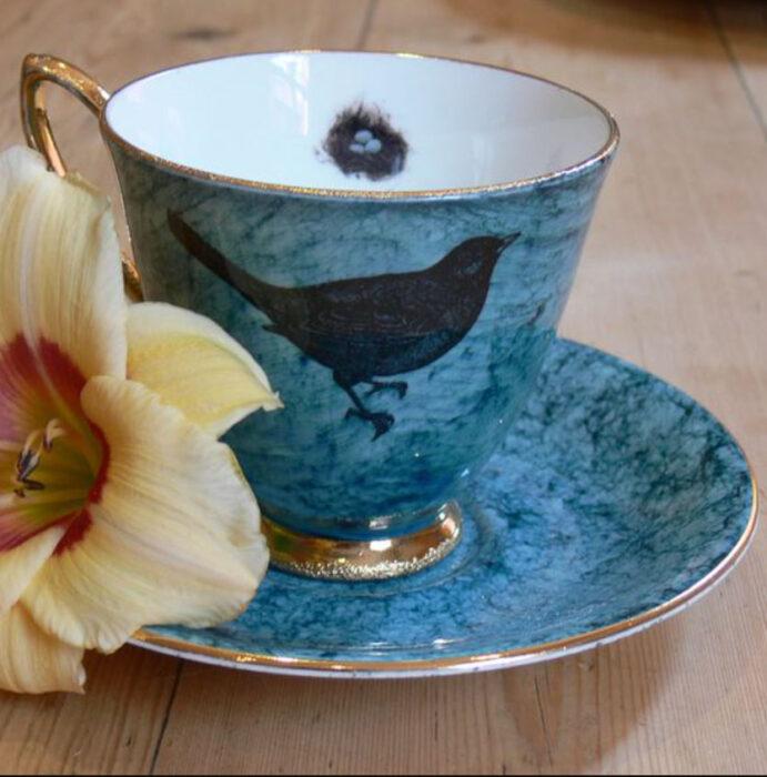 Taza para tomar el té, de color azul, con un cuervo pintado en ella