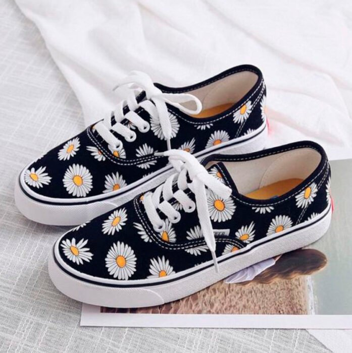 Black sneakers with hand-painted daisies all over the fabric