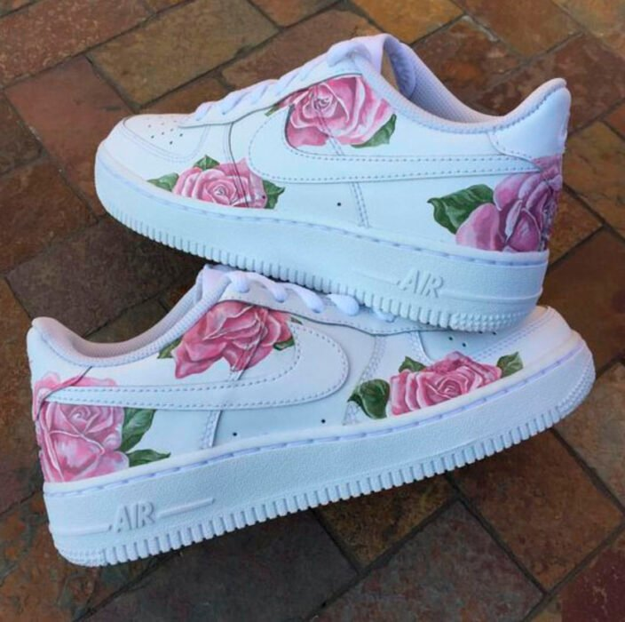 White tennis shoes with hand-painted pink roses over the entire tennis court.
