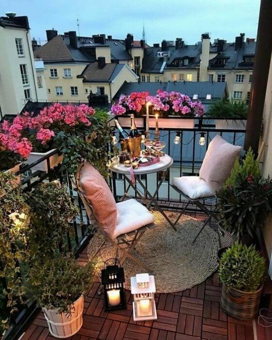 Decoración de terraza en colores claros con detalles de plantas alrededor