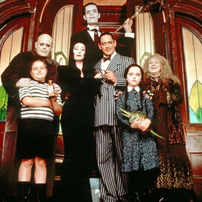 Elenco de Los locos Addams frente al pórtico de su casa