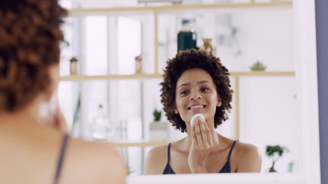 Girl removing makeup in front of the mirror