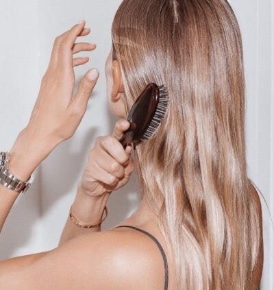 chica rubia cepillando su cabello
