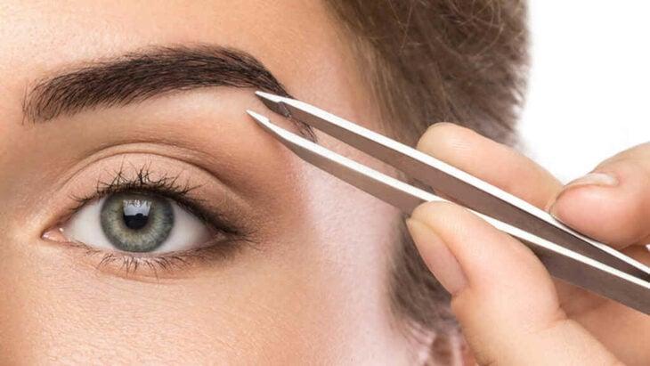 Mujer sacándose las cejas con pinzas