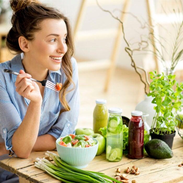 Chica sentada comiendo ensalada