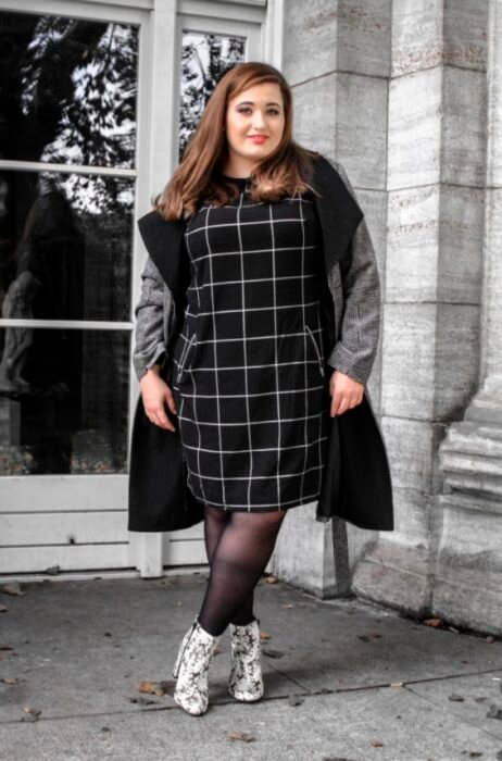 Curvy girl wearing a black dress with white squares, gray blazer, black stockings and python boots