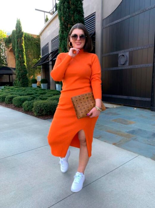 Curvy girl wearing an orange dress, with white tennis shoes