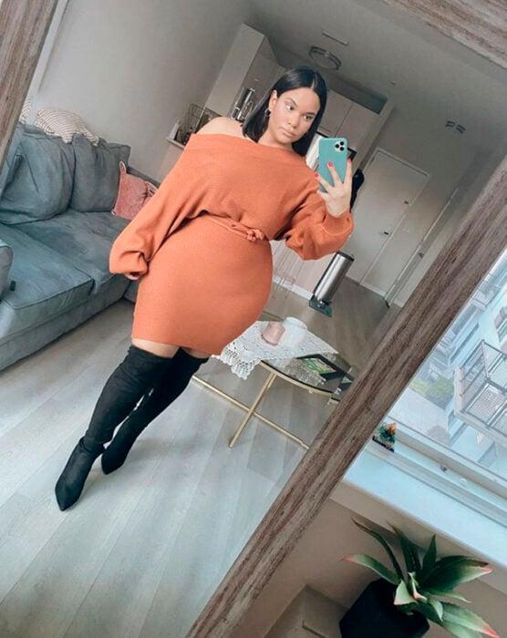 Curvy girl wearing peach dress, black high boots and belt