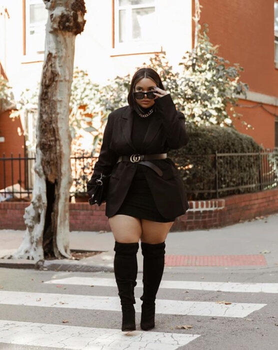 Curvy girl wearing a black dress, black blazer and belt, along with high boots