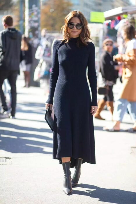 Girl wearing a long knitted dress in black color
