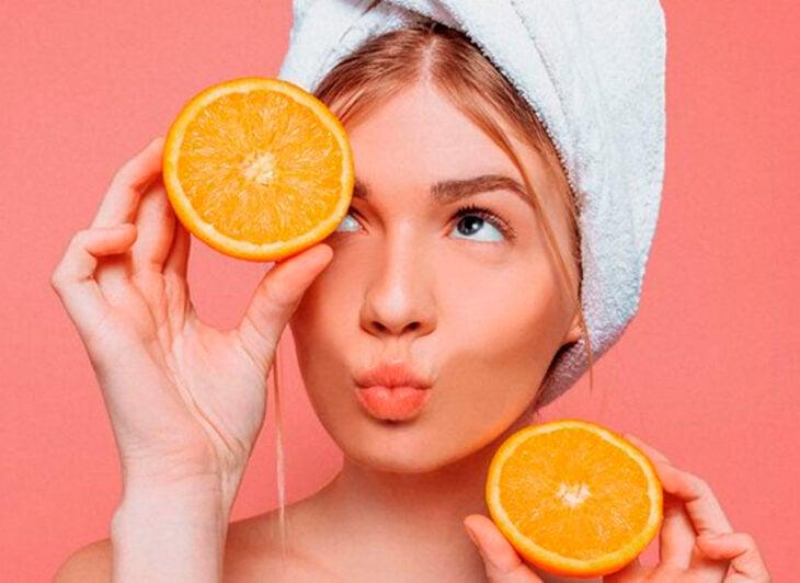 Chica con toalla en la cabeza, y sosteniendo mitades de naranja