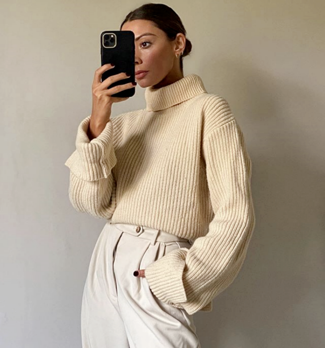 brown haired girl wearing beige knit top with high neck and long sleeves, white dress pants at the waist