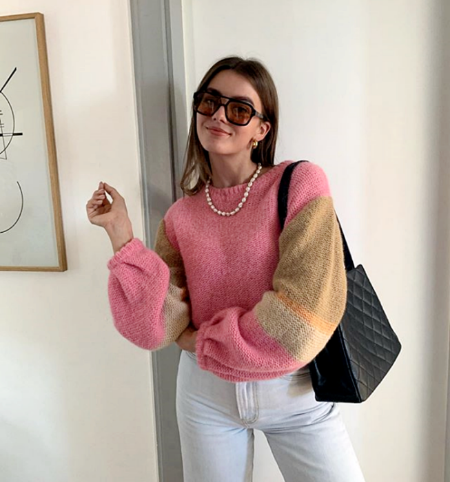 brown haired girl wearing sunglasses, pink and brown knitted blouse and beige, jeans at the waist and square black handbag