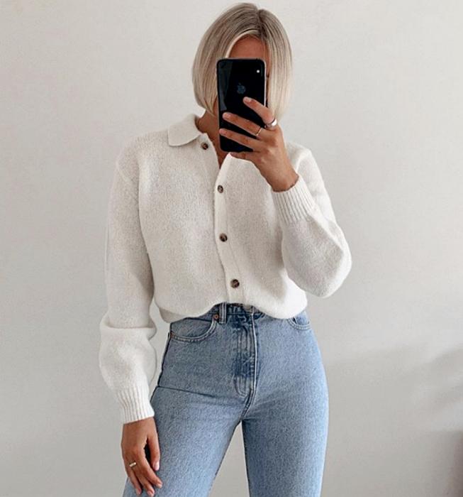chica de cabello platinado usando un top blanco de botones con mangas largas y skinny jeans a la cintura