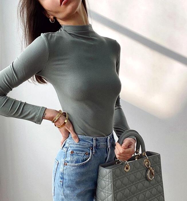 chica de cabello largo usando un top verde claro de manga larga y cuello alto, jeans a la cintura y bolso de mano color verde claro
