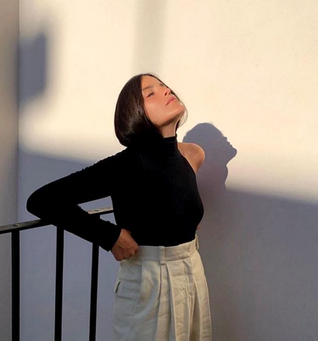 chica de cabello castaño usando una blusa negra con una manga larga y una corta, pantalón de vestir beige