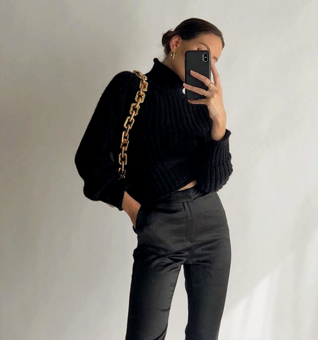 brown haired girl wearing black knitted top with high neck and long sleeves, gold chunky chain black bag, satin dress pants