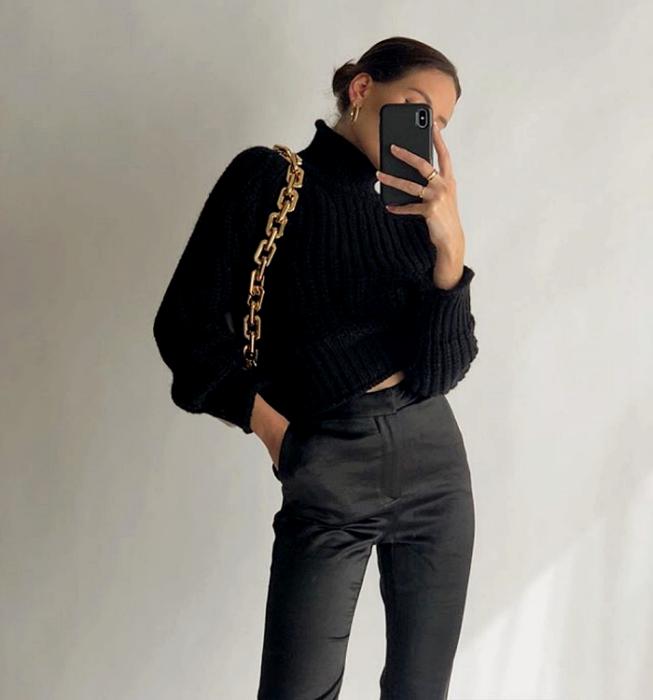 chica de cabello castaño usando un top negro tejido de cuello alto y mangas largas, bolso negro de cadena gruesa dorada, pantalón de vestir de satén