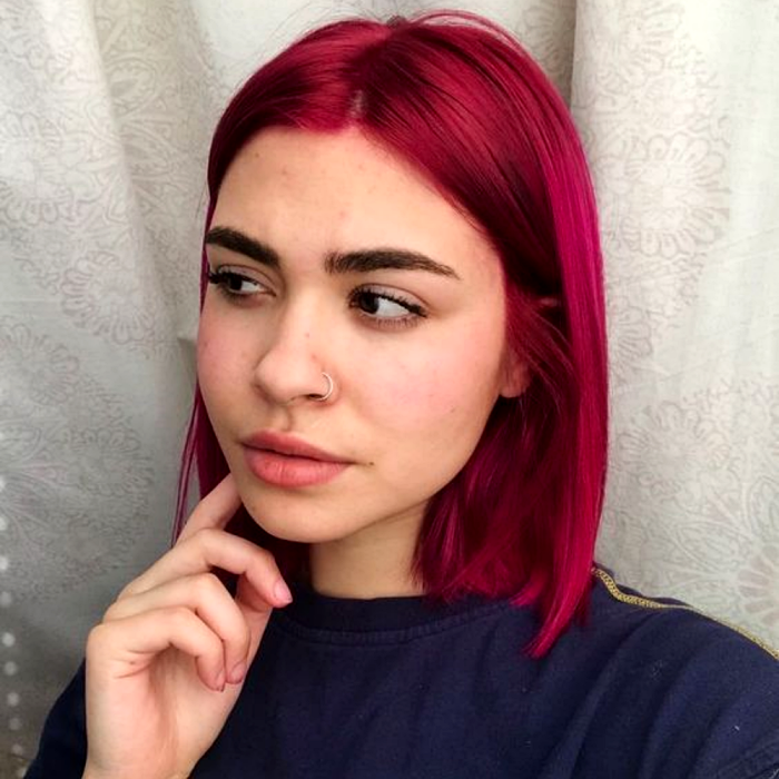 short hair girl dyed hot fuchsia pink, wearing navy blue t-shirt