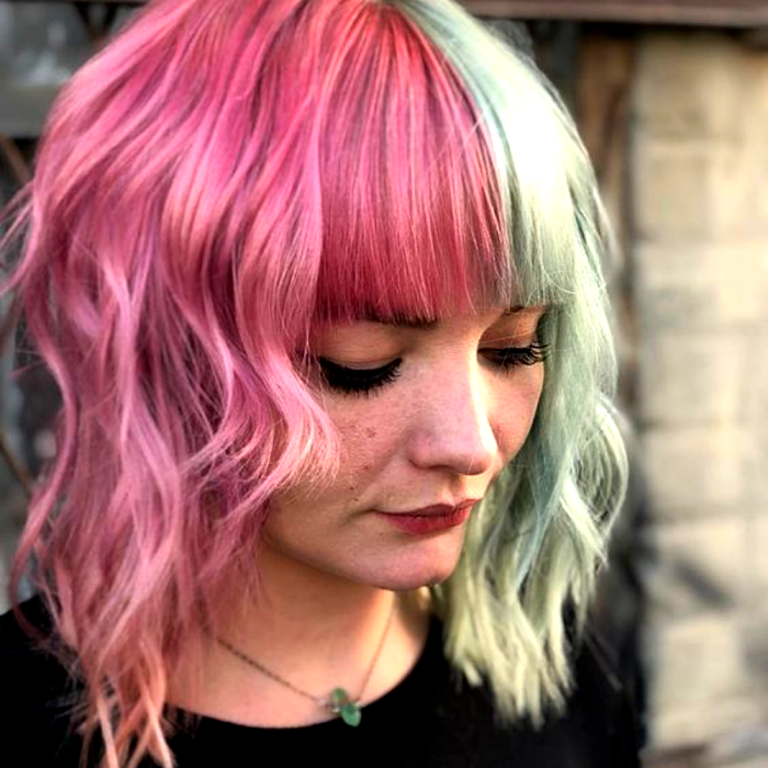 short hair girl dyed pink and pastel green, half and half. wearing a black crew neck t-shirt