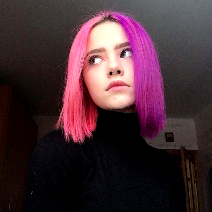 girl with short hair dyed neon pink and purple, half and half. black high neck long sleeve top