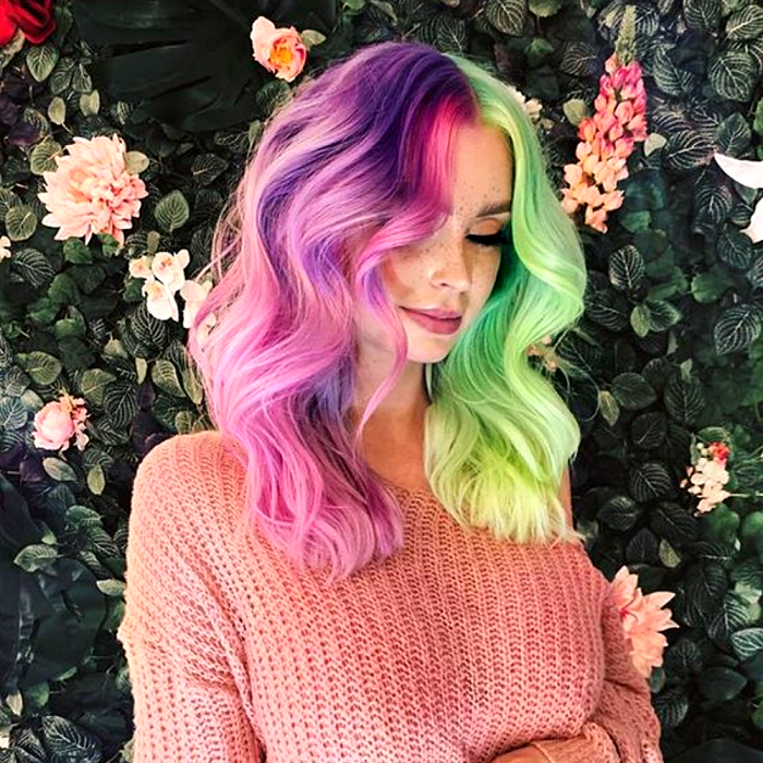girl with half and half pastel purple and green dyed hair. wearing a pastel pink knitted long sleeve sweater
