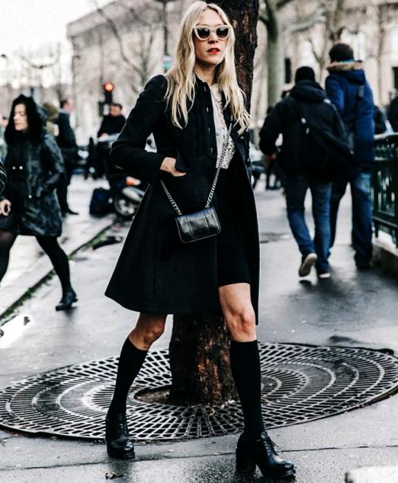 chica rubia usando lentes de sol, camisa de vestir blanca, abrigo negro largo, minifalda negra, calcetas negras largas, zapatos de plataforma negros y bolso mini negro
