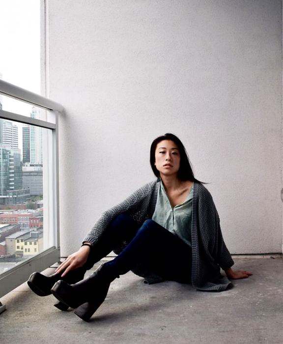 chica de cabello negro usando una camisa gris, cárdigan gris, skinny jeans y botines negros de plataforma