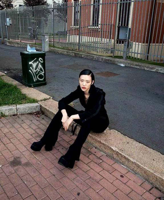 chica de cabello oscuro usando un saco negro, pantalones de vestir negros y botas de plataforma negras