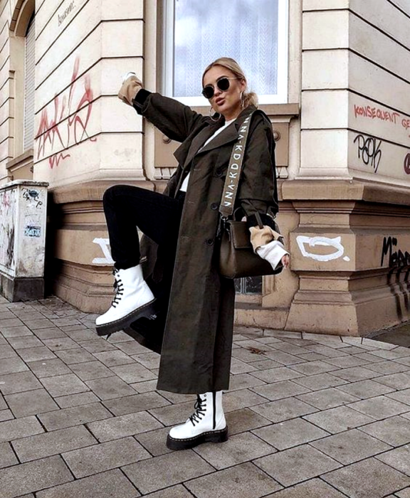 chica rubia usando lentes de sol, camiseta blanca, leggings negros, botines blancos de plataforma negra, abrigo largo café oscuro y bolso café de piel