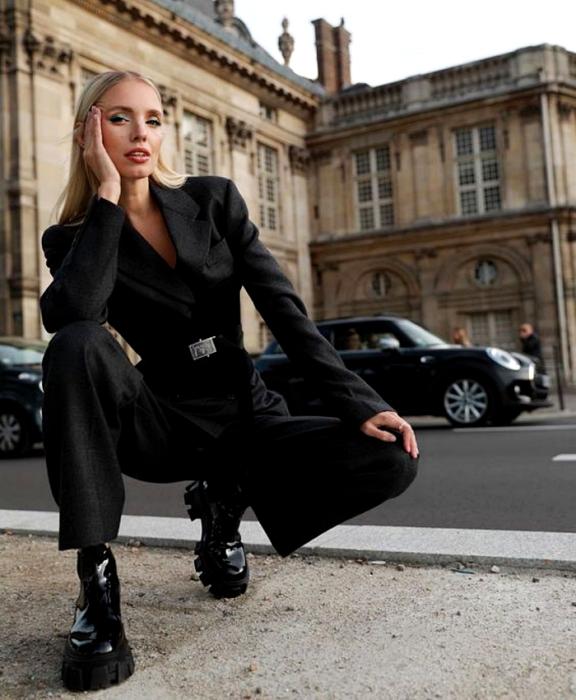 chica rubia usando traje formal negro, blazer negro, cinturón negro, pantalones de vestir negros y botines negros de plataforma