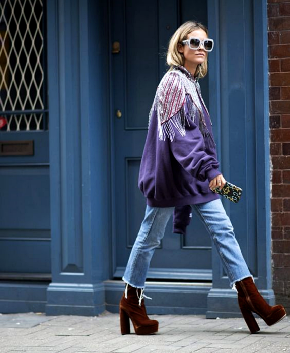 blonde girl wearing sunglasses, purple sweatshirt with shoulder appliqués, cropped jeans and red velvet platform shoes
