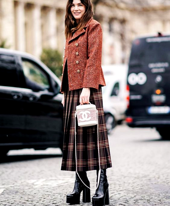 brown haired girl wearing red coat with gold buttons, black checked maxi skirt with red and coffee, black platform boots and white channel bucket bag