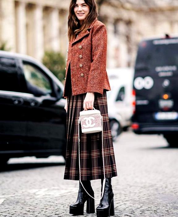 chica de cabello castaño usando un abrigo rojo con botones dorados, falda maxi de cuadros negros con rojo y café, botas de plataforma negras y bolso channel blanco bucketbag