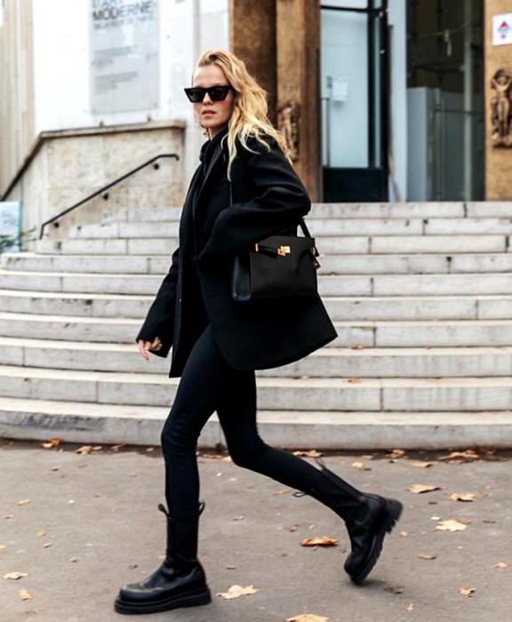 chica rubia usando lentes de sol, abrigo negro, leggings negros, botines de plataforma negros de piel y bolso negro de piel