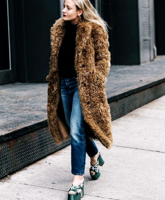chica rubia usando top negro, abrigo largo afelpado, jeans a la cintura y sandalias de tacón de plataforma verdes con decoraciones blancas