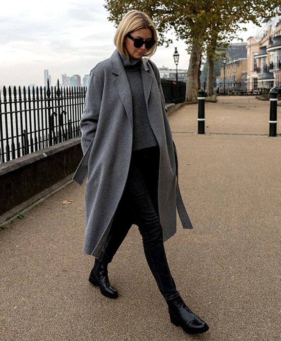 chica rubia con lentes de sol, usando un suéter gris, abrigo largo gris, skinny jeans negros, botines negros de tacón pequeño