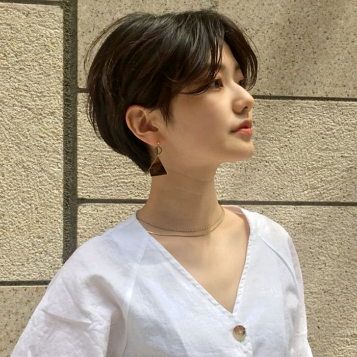 girl with layered pixie haircut, white V-neck top