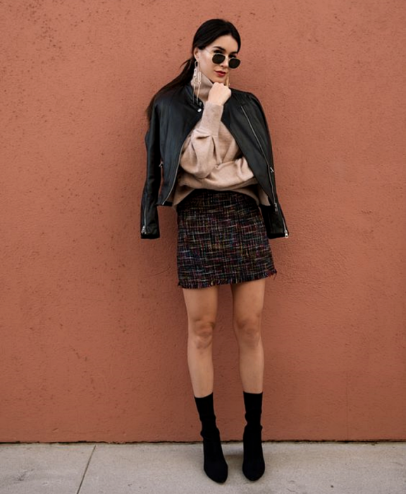 dark haired girl wearing sunglasses, beige long sleeve sweater, leather jacket, black mini skirt knitted with white lines, black sock boots style