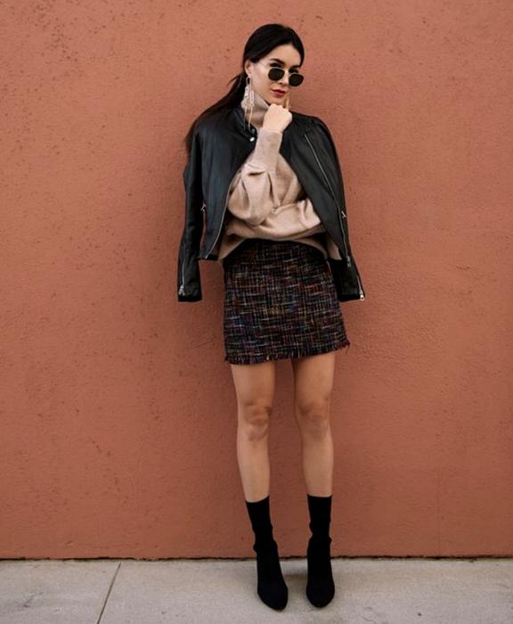 chica de cabello oscuro usando lentes de sol, suéter beige de manga larga, chaqueta de cuero, minifalda negra tejida con líneas blancas, botines estilo sock boots negras